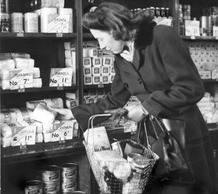 Black and white photo of a woman shopping at The Co-op